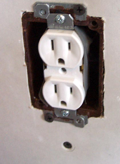 picture of the wall with outlet box and outlet mounted into hole
